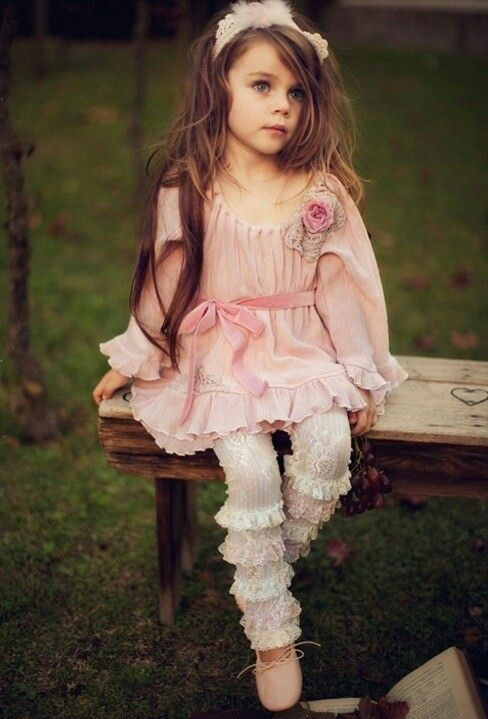 Beautiful little girl with long brown hair sitting on a bench with a pink  dress a