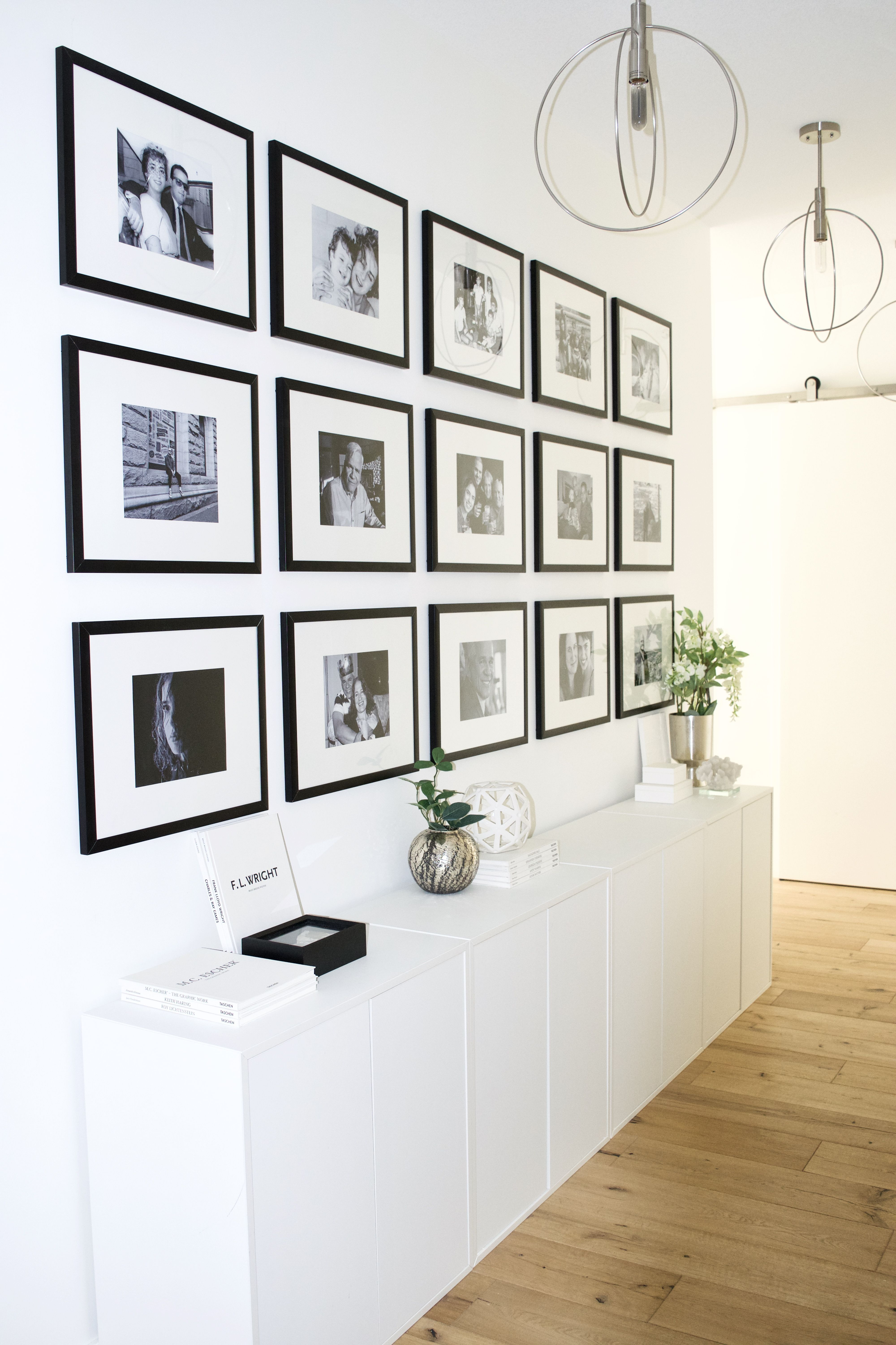 This hallway is right off the entrance of a beautiful modern Scandinavian apartment. A low bank of white Ikea Eket cabinets and a grid of black and white family photos create a carefully curated focal point for guests as they enter, and provides extra storage for small space living.This #hallway #is #right #off #the #entrance #of #a #beautiful #modern #Scandinavian #apartment. #A #low #bank #of #white #Ikea #Eket #cabinets #and #a #grid #of #black #and #white #family #photos #create #a #carefull