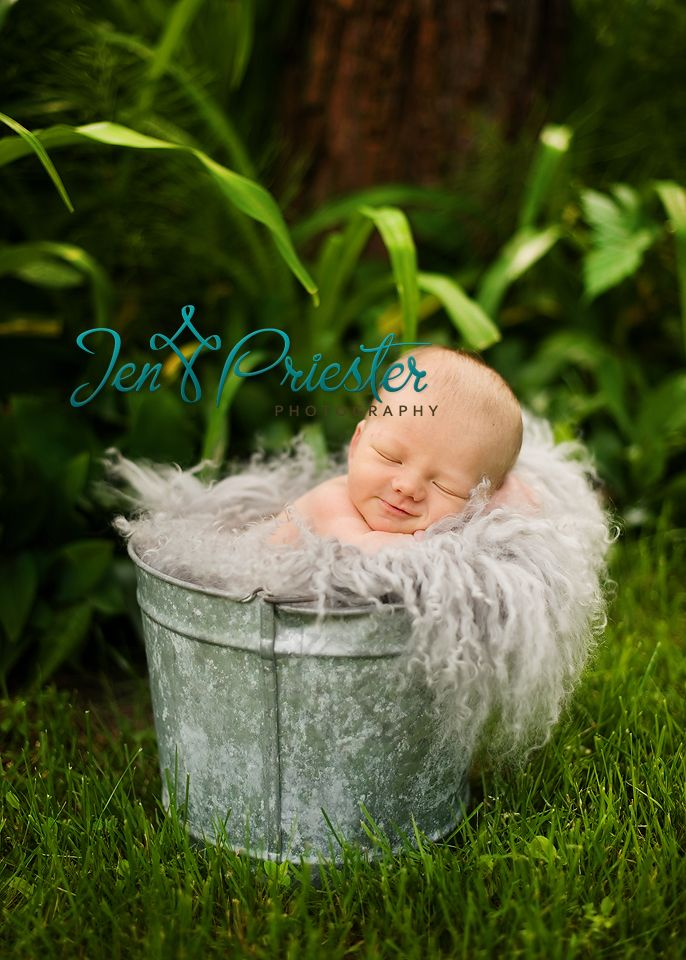 Smiling newborn posed bucket outside michigan photos
