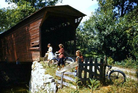 Women riding bicycles stop a covered bridge1949