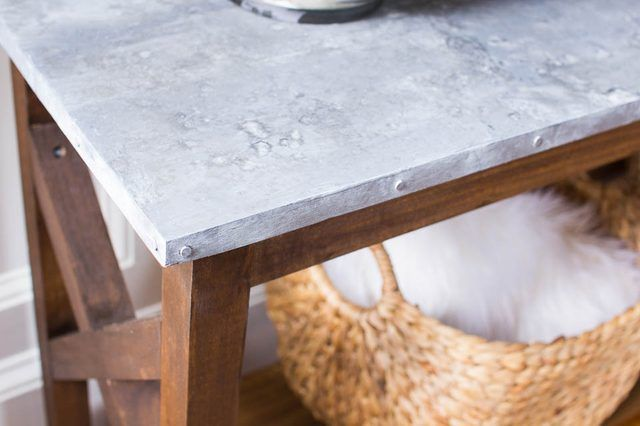 Make your own sofa table and create a faux galvanized top with paint. You will be surprised how real it looks!  An easy DIY with a high end look.