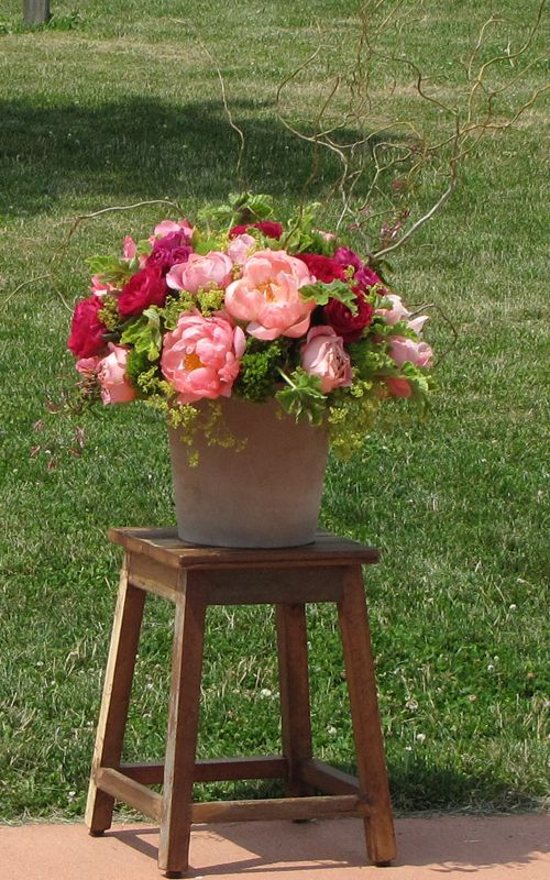 Earthy clay pots with a base of mossy greens and branches were topped off with garden roses, peonies and sweet pea.