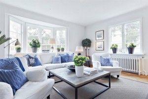 New England-talon valkoinen ja valoisa olohuone, jossa väriä tuovat vaaleanfarkunsiniset tyynyt.