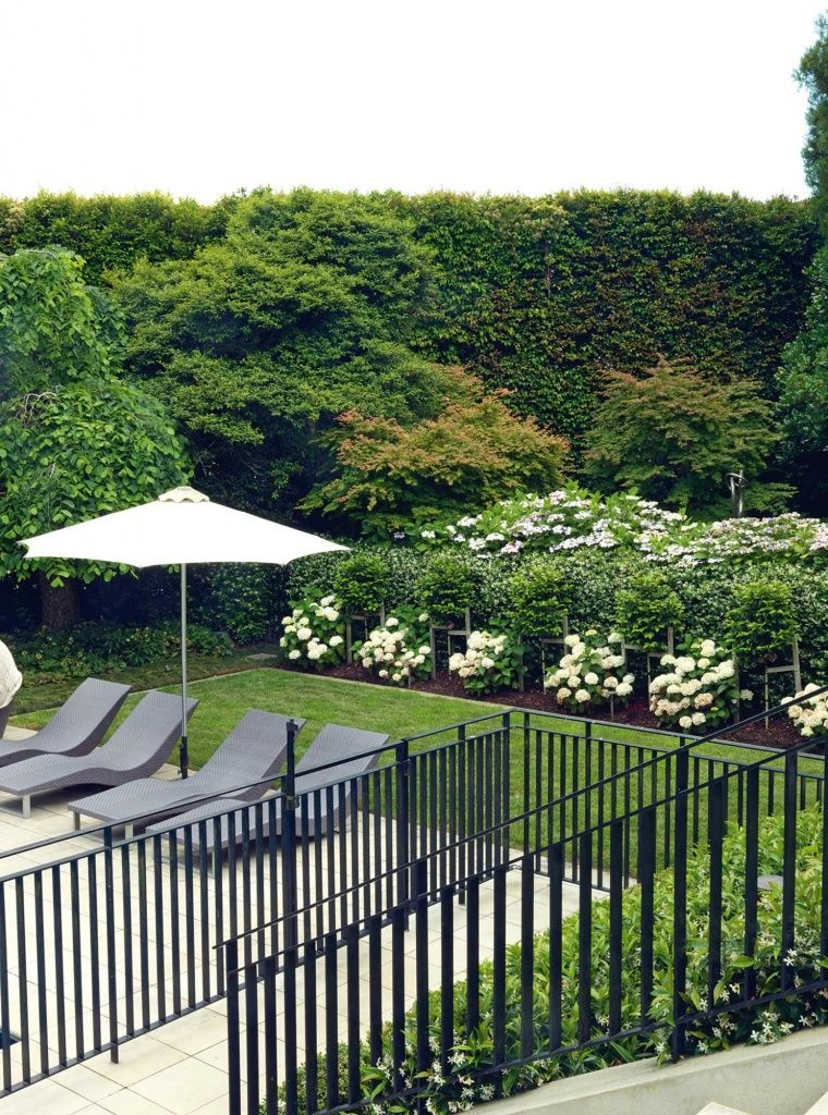 A custombuilt wroughtiron pool fence fits the style of