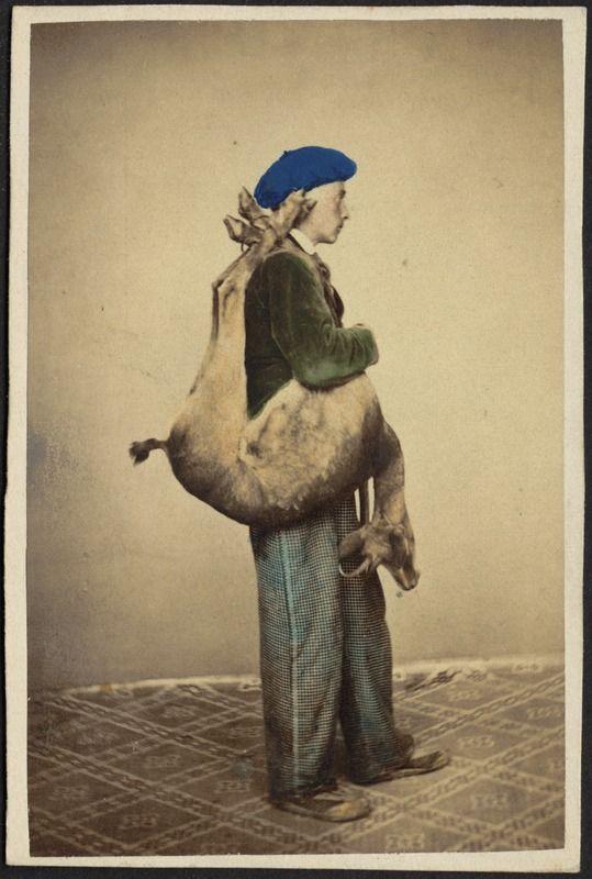 Studio portrait of young man in beret with dead deer slung over shoulder.