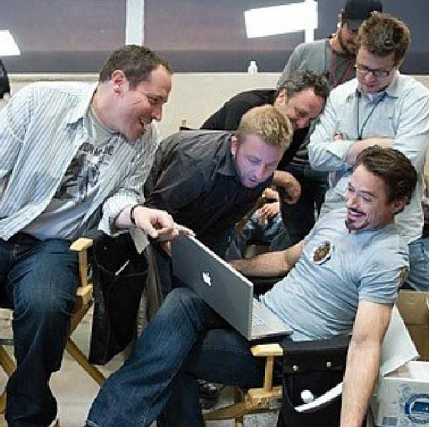 """Robert Downey Jr., Jon Favreau and crew watch something entertaining (daily rushes?  Or """"General Hospital""""?)."""
