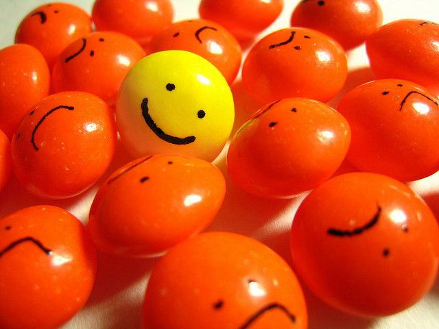 yellow smiley face in a group of orange sad faces