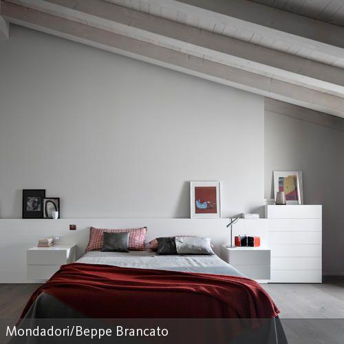 Das Schlafzimmer mit Dachschräge wurde mit einem weißen Sideboard und Bett mit roter Tagesdecke zweckdienlich und gemütlich gestaltet. Auf dem Wandvorsprung…