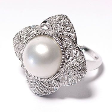 A 1930's styled silver ring set with a synthetic button top pearl & cubic zirconia. The underside of this ring is worth mentioning as the workmanship has gone a step futher with the attention to detail.