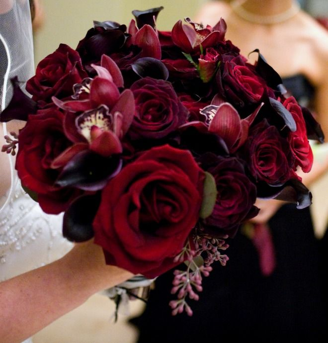 Deep reds and wine colored bouquet of roses, calla lilies and ...