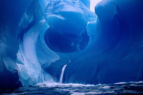 Sculptured rare Blue Iceberg, compressed & shaped by the sea. Antarctica.