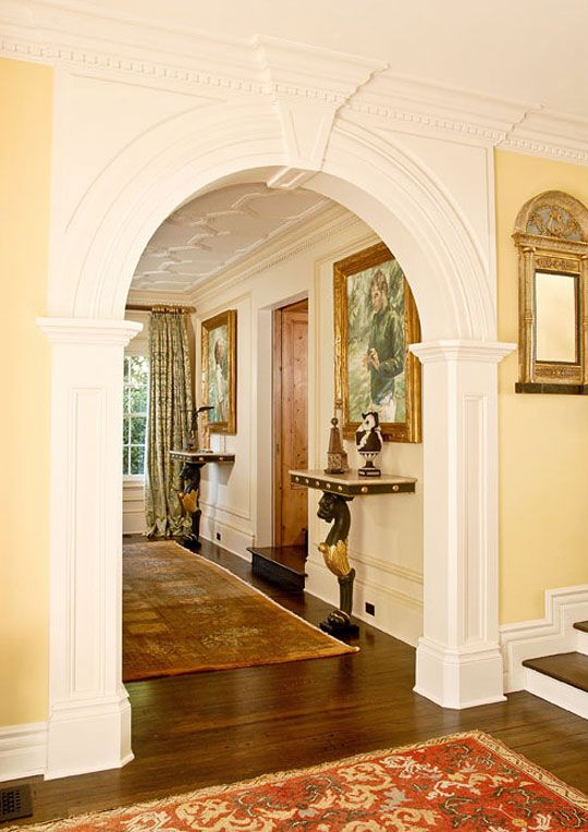 An elegantly trimmed arch connects the grand foyer with living room  Traditional Home Hollywood Before After Foyers Arch and