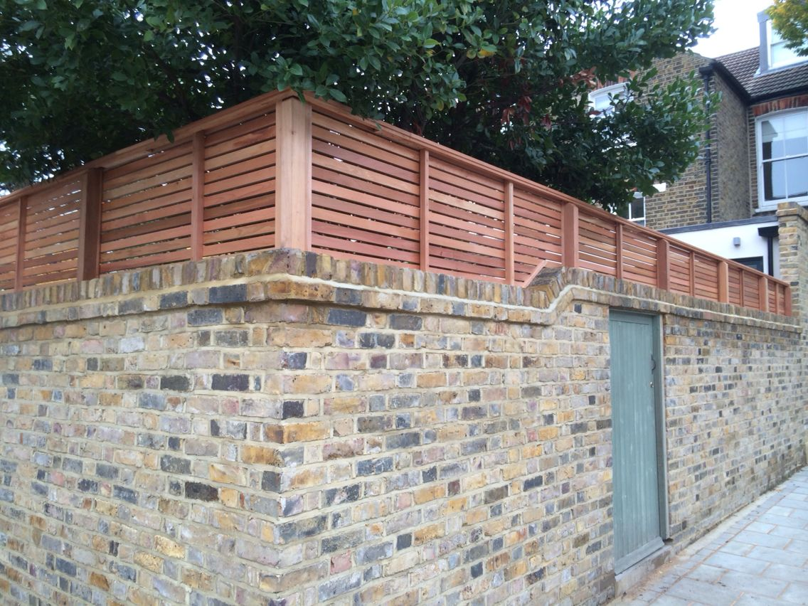 Cedar Slatted Fencing On Top Of A Brick Wall This Is The Rear View Of How Our Fence Panels Look Www Contemporaryfenci Brick Wall Gardens Pergola Fence Panels