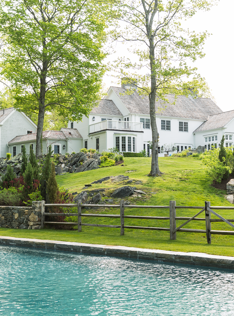 Beautiful pool behind a classic all-white Colonial style home.