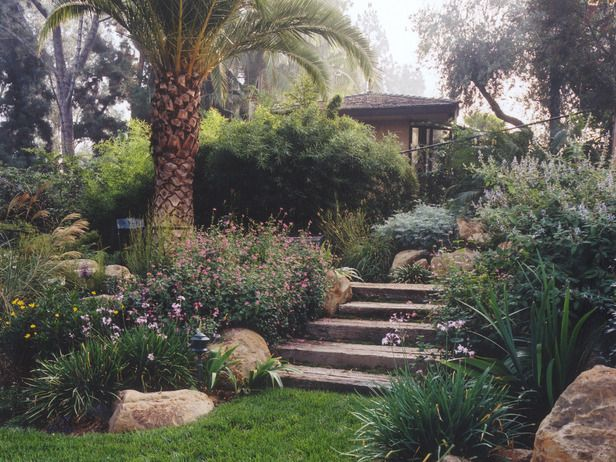 12 Budget Friendly Backyards Old World Style Stairs Guide Visitors Through Lush Gard Large Backyard Landscaping Landscaping With Rocks Cheap Landscaping Ideas