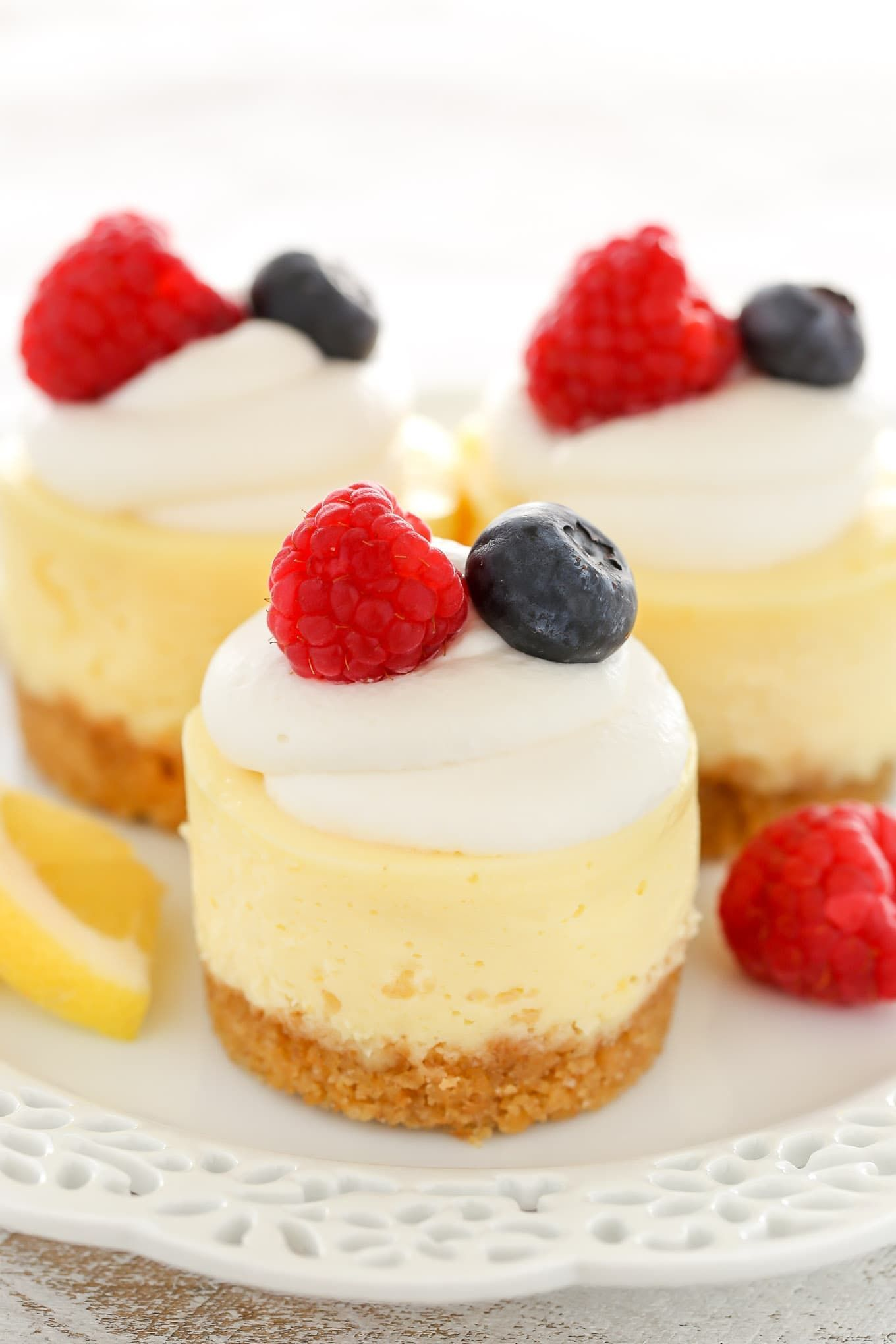 These Mini Lemon Cheesecakes feature an easy homemade graham cracker crust topped with a smooth and creamy lemon cheesecake filling. Top them with some fresh whipped cream and berries for an easy dessert everyone will love! #homemadegrahamcrackercrust These Mini Lemon Cheesecakes feature an easy homemade graham cracker crust topped with a smooth and creamy lemon cheesecake filling. Top them with some fresh whipped cream and berries for an easy dessert everyone will love! #homemadegrahamcrackercrust