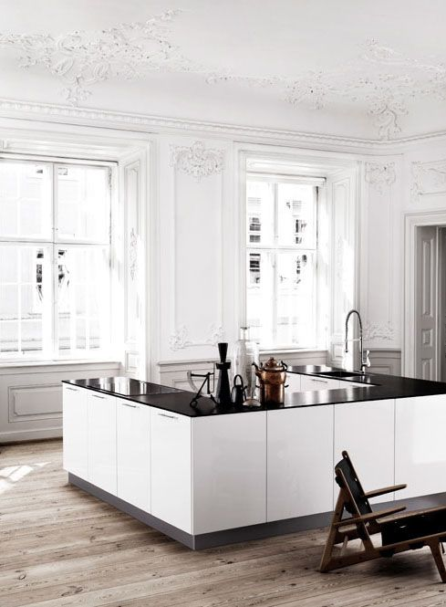 Gorgeous minimalist style kitchen. Love the weathered wood floors with white walls and decorative moulding!