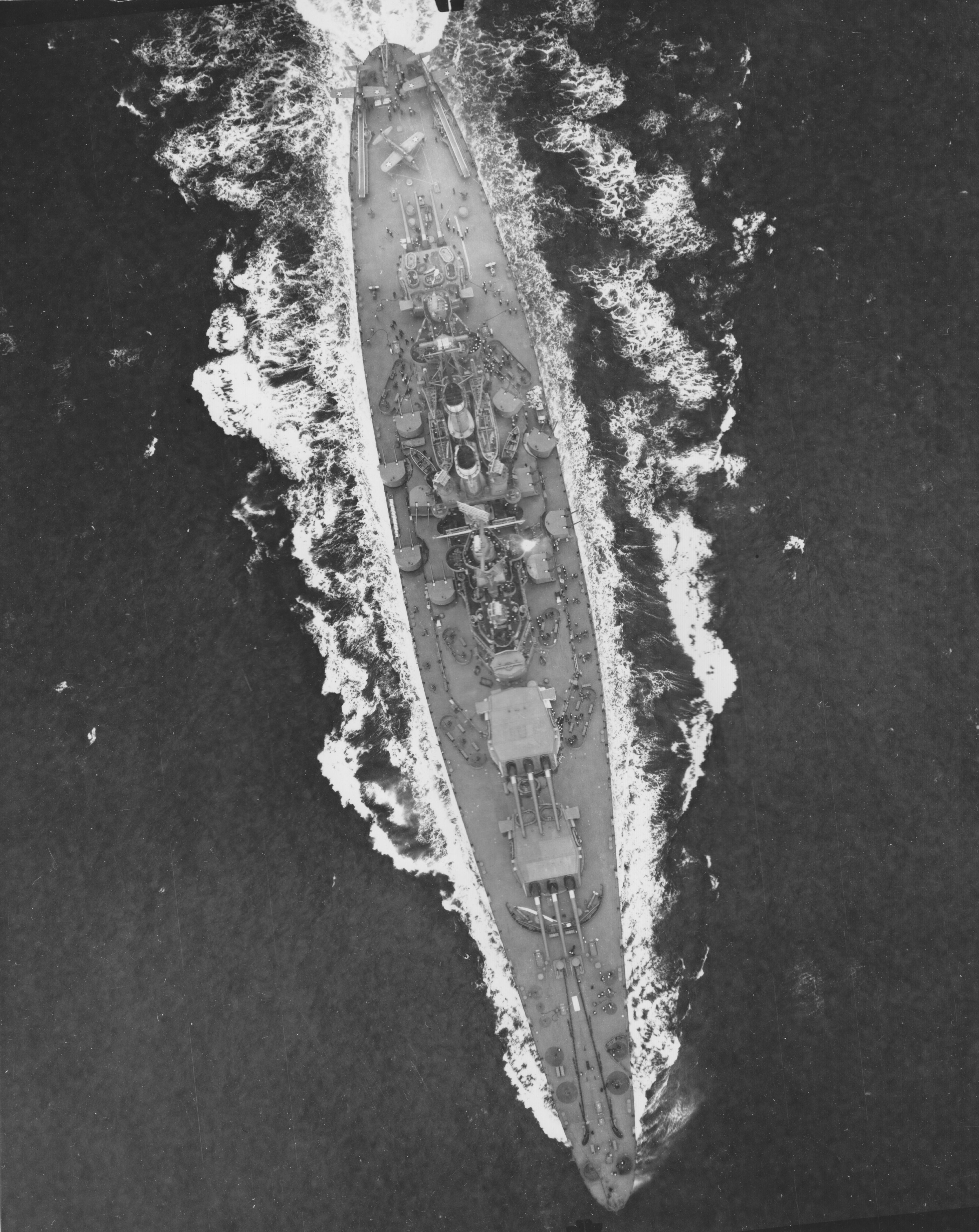 A majestic aerial photo of USS North Carolina (BB-55) demonstrating all the fine details of her armament and general disposition of superstructures. Despite her size, she is as handsome as she is powerful. A splendid view captured on April 17, 1942.