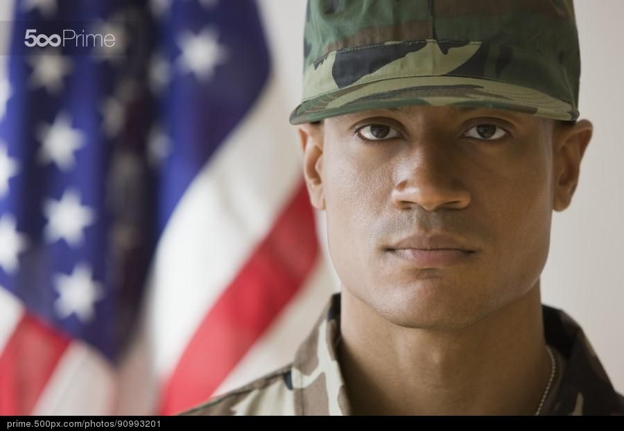 African male soldier in front of american flag stock