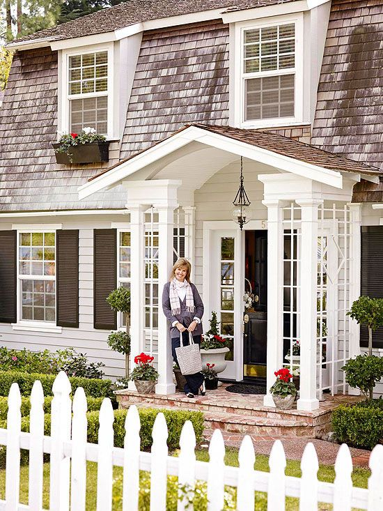 Layer On the Charm Polish your home's exterior with details. Entry addition features a portico with elegant trim, outdoor lighting, and a glossy black door with sidelights. Window boxes, a white picket fence, and a brick pathway framed by shrubs amplify the home's charm.