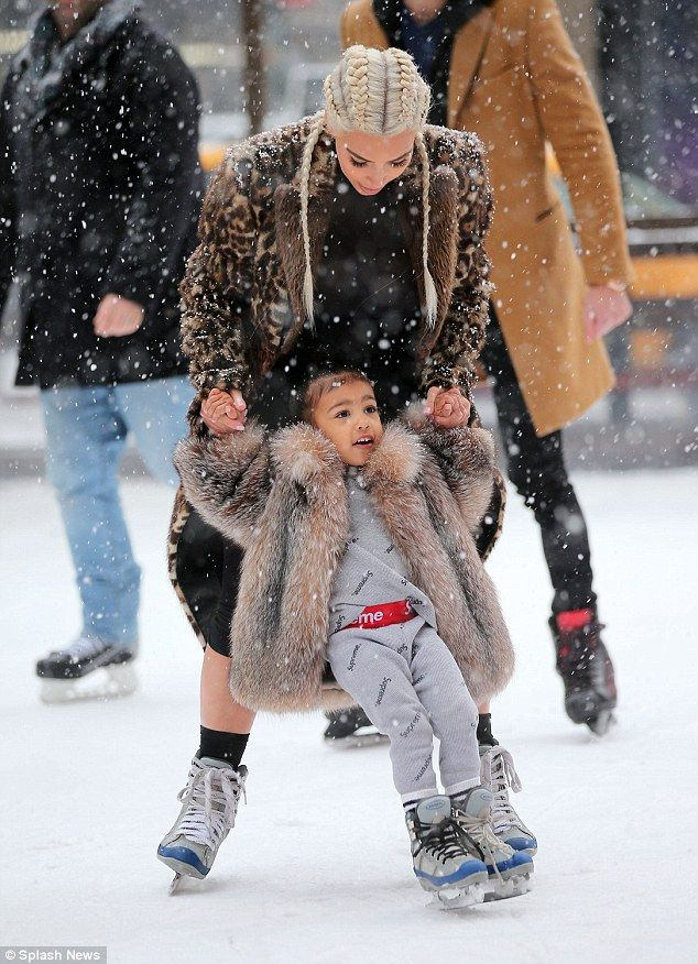 Easy does it! The two-year-old tot wrapped up warm in a grey tracksuit and coat, while 35-year-old Kim went for a glamorous look, her white-blonde hair in tight braids and with an oversized fur coat over her ensemble