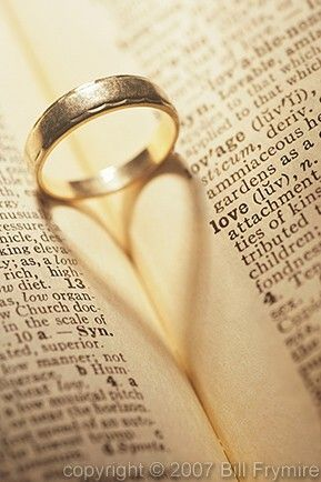 Place both wedding rings in Bible on scripture about lovemarriage