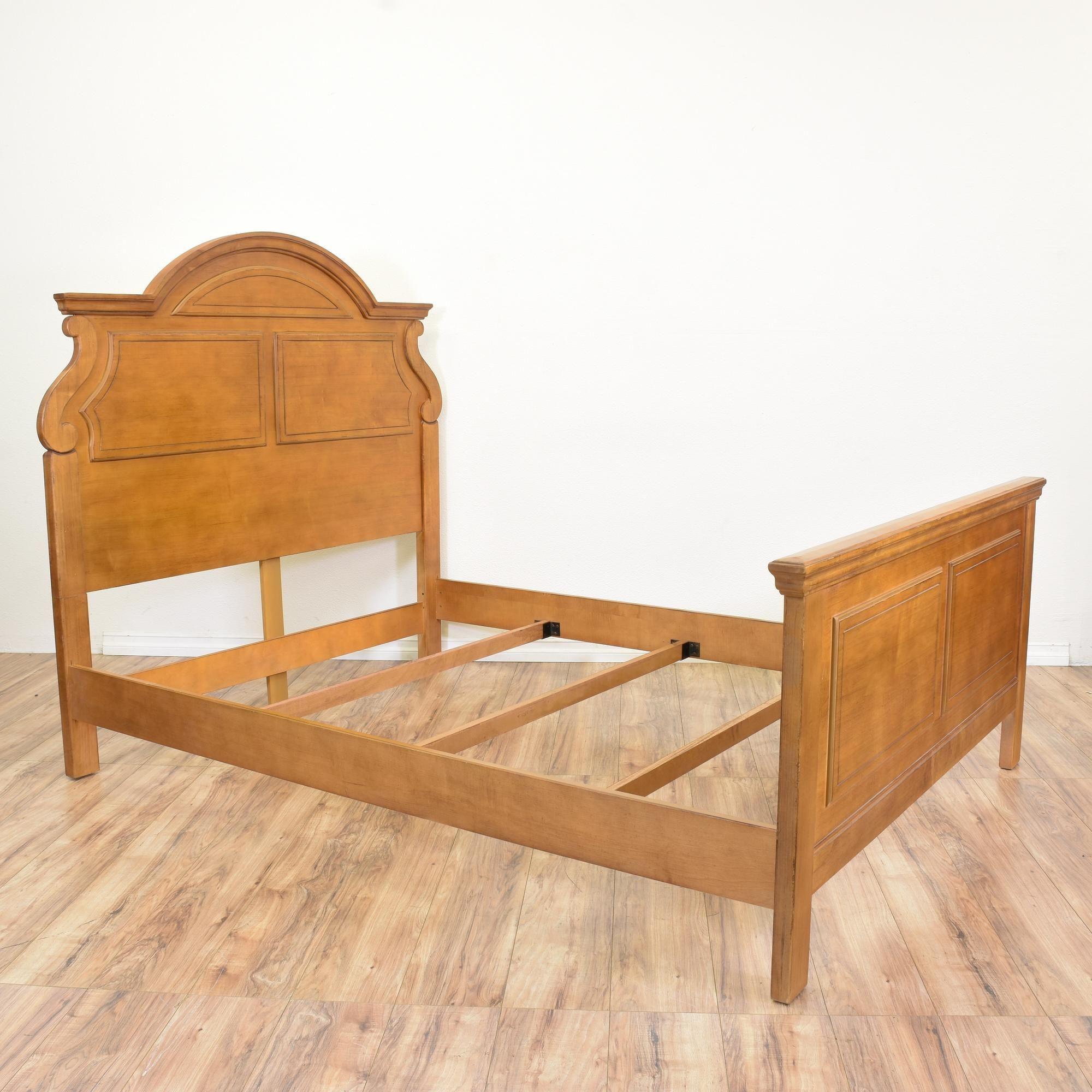 This queen sized bed frame is featured in a solid wood with a glossy ...