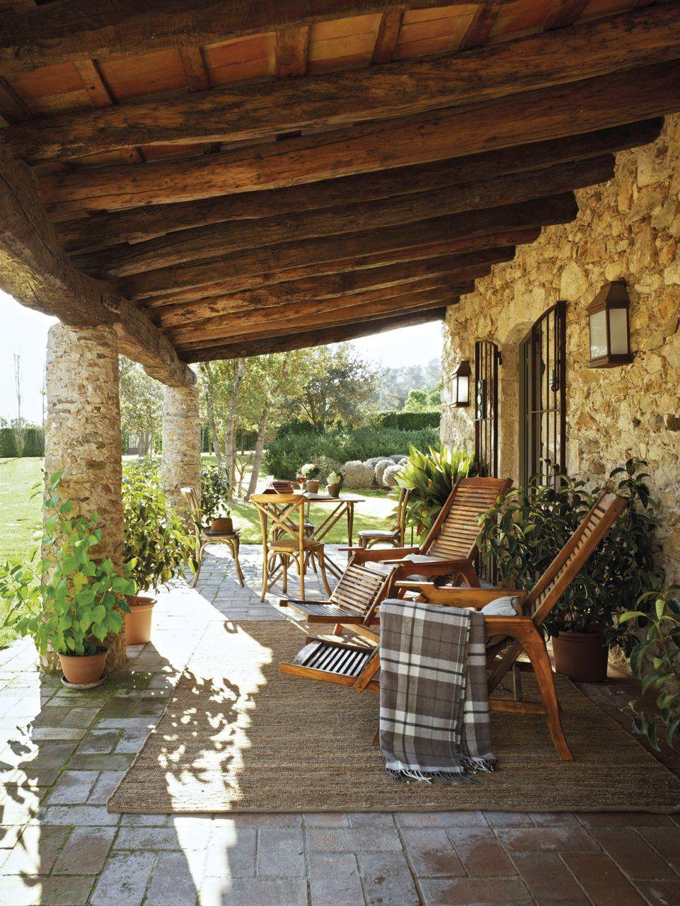 porche con columnas de piedra y techo de madera