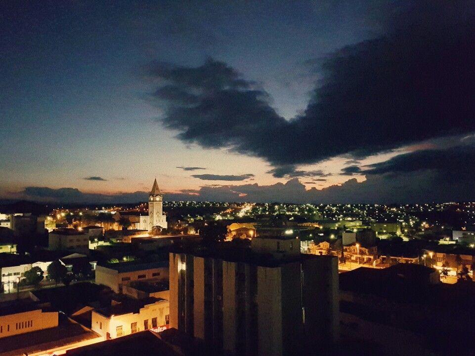 Nuvens escuras e luzes artificiais num pôr-do-sol em Araxá.