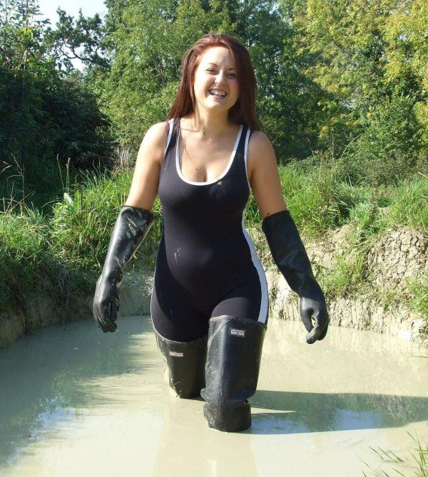 Amateur in spandex bodysuit, waders, and gloves in mud.