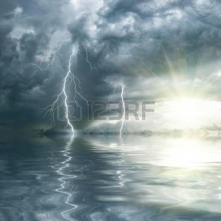 Tormenta con lluvia y truenos sobre el oc�ano, el sol brilla a trav�s de las nubes photo