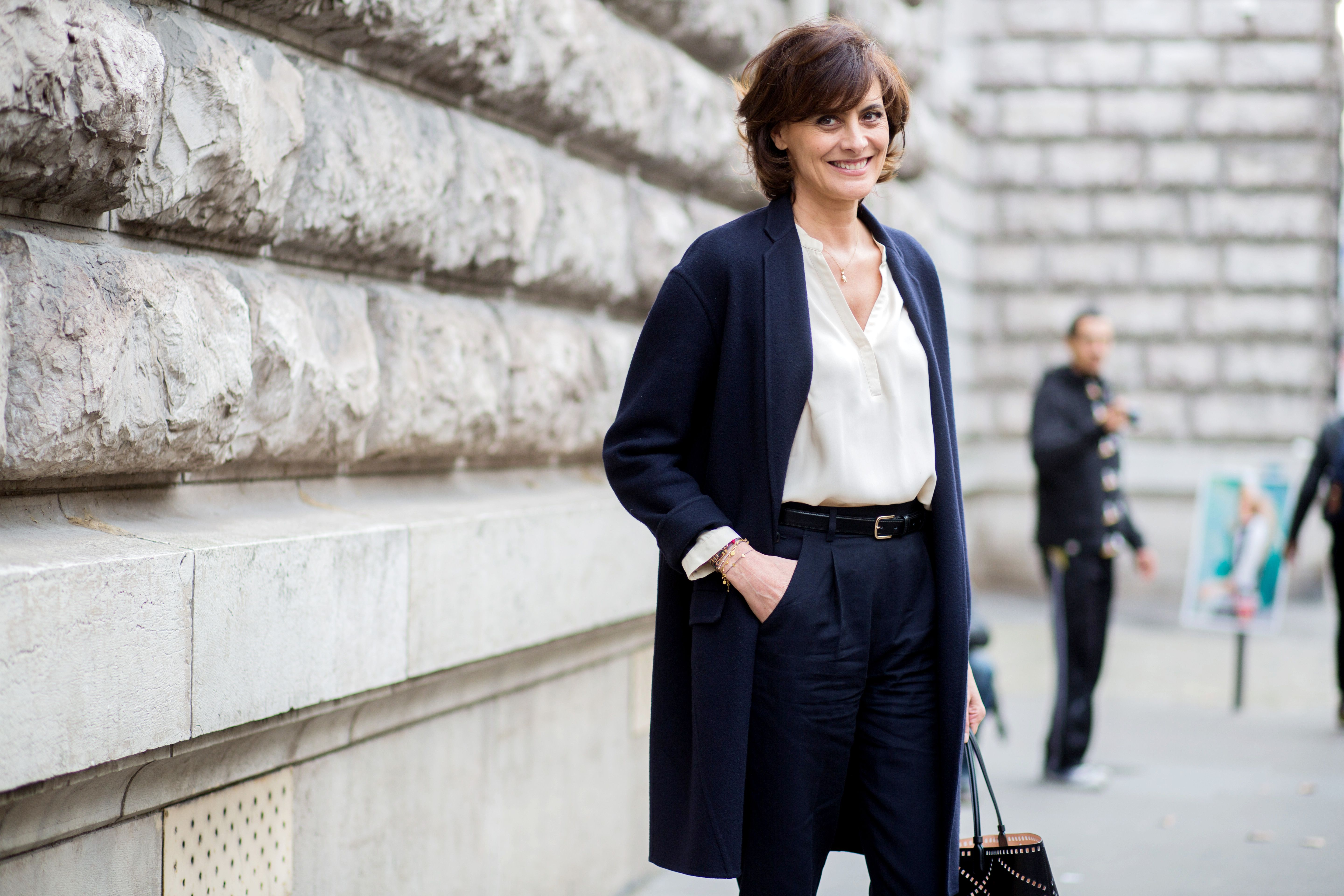 Classic navy coat worn with a blouse tucked into high-waisted trousers at Paris Fashion Week // Photo: The Stylograph