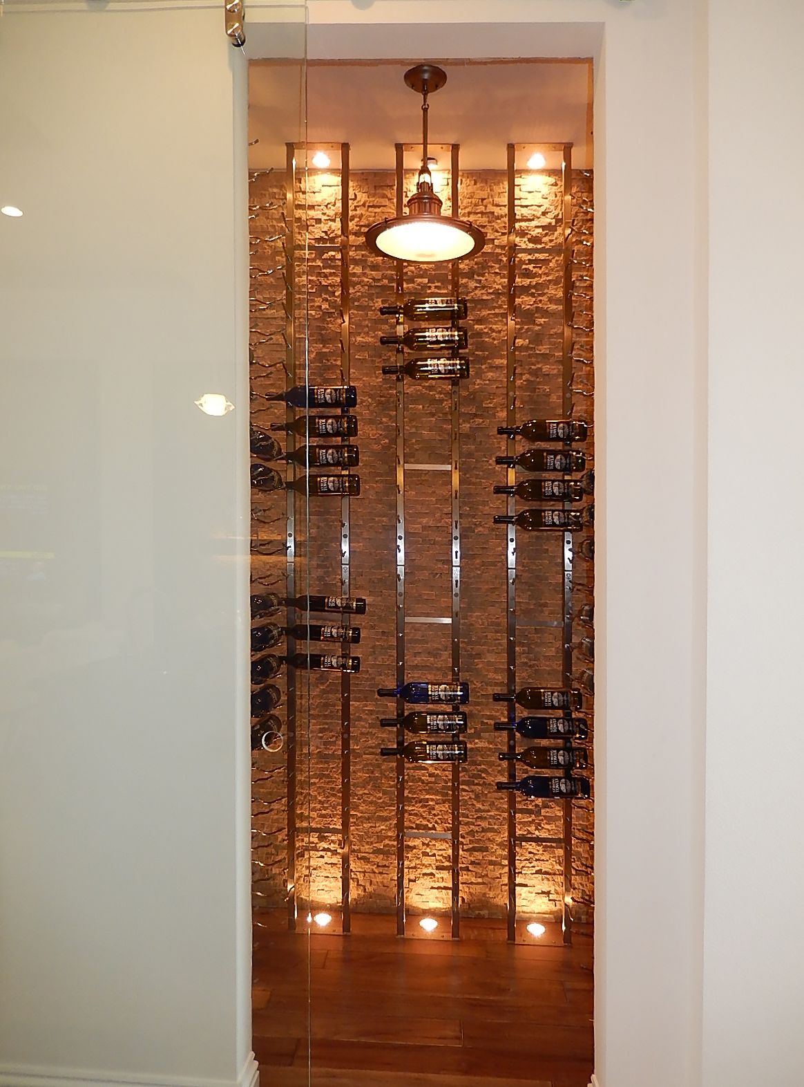 This wine cellar in a model home features floor to ceiling wine this wine cellar in a model home features floor to ceiling wine holders with cultured stone background wall and lighting on floor and ceiling for accent arubaitofo Choice Image