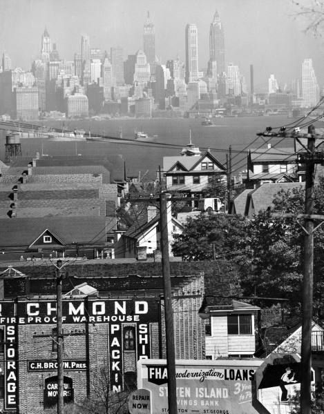 Distant view of lower Manhattan and ferry docks as seen with the aid of a telephoto lens over the rooftops of buildings in Staten Island, 1946, Andreas Feininger