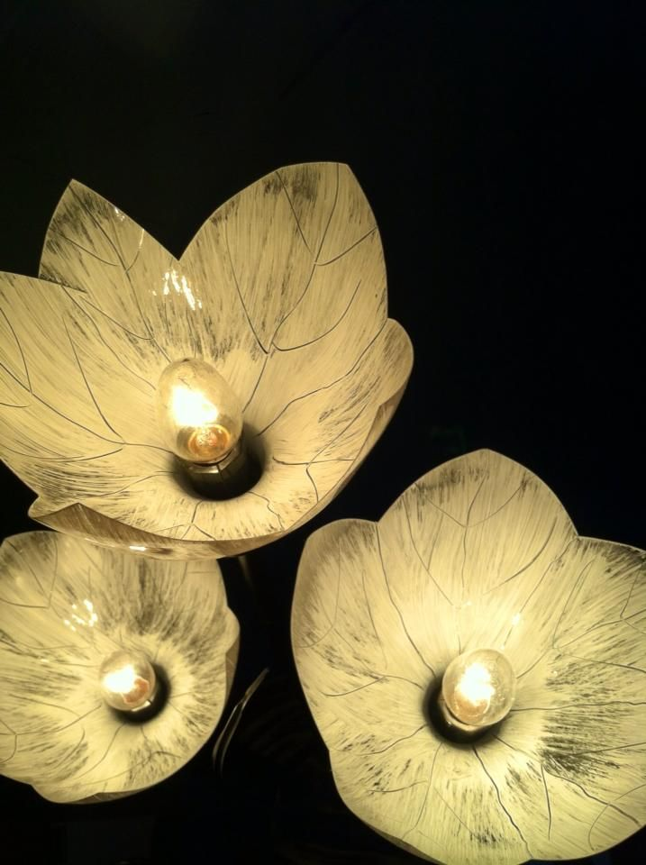 I made these three flower shades from the tops of recycled pop bottles...cut to shape..the top of the bottle slips right through this old lamps three little outlits just perfect to size...dry brushed with a bit of white paint and some simple leaf detail drawn with a tootpick while paint is still wet..