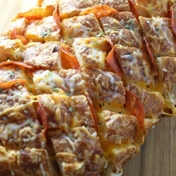 This Pepperoni Pizza Pull Apart Bread is sourdough bread drenched in buttery garlic then stuffed with pepperoni and cheese for melty, gooey pizza goodness!