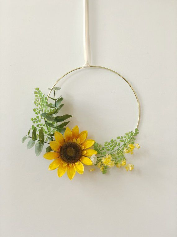 Floral Spring Wreath Beautiful, modern wreath arranged with eucalyptus, green spray, and accented with a gorgeous silk sunflower. Supported by a 11 gold hoop that modernizes this beautiful, decorative item. Attached ribbon will be given with the order. Perfect for summer and fall or #sunflowerbedroomideas