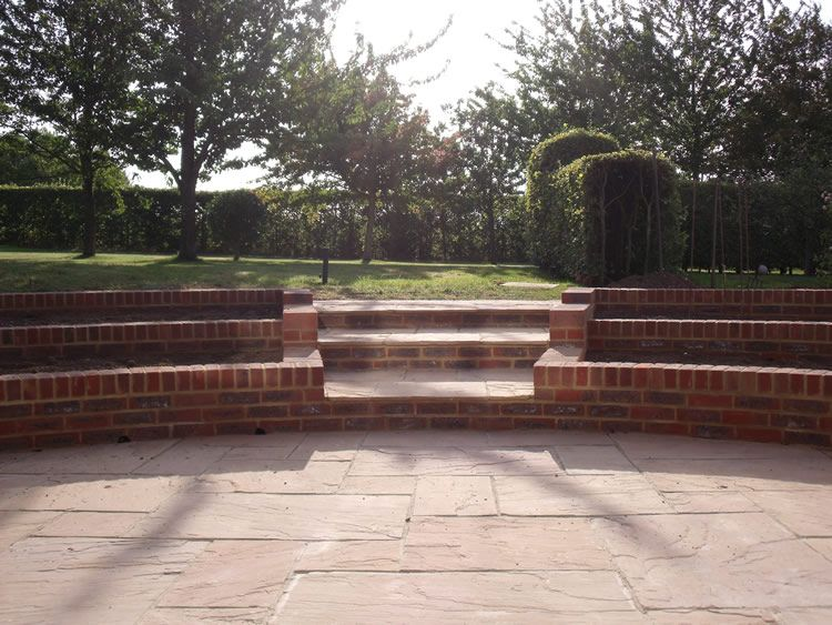 Indian Sandstone Patio Complimented With Beautiful Curved Brick Planters.