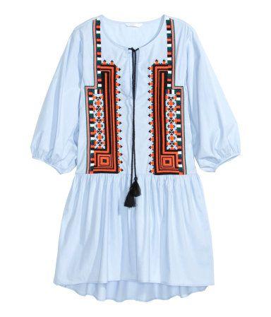 Lyhyt ja väljä mekko ilmavaa puuvillapopliinia. Solmittavat nauhat ylhäällä ja kirjailtu etukappale. 3/4-hihat, joissa joustava suu. Rypytetty lantioleikkaus ja hieman pidempi takakappale.