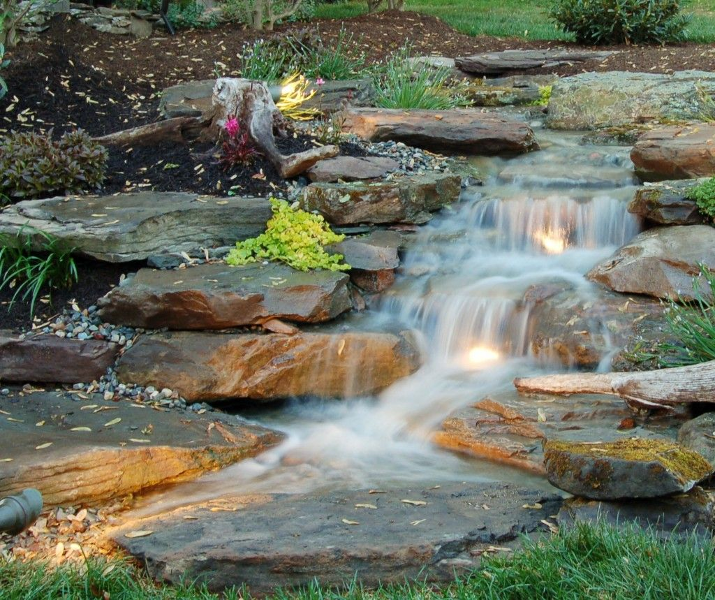 Lighted natural pondless waterfall www for Pictures of backyard waterfalls