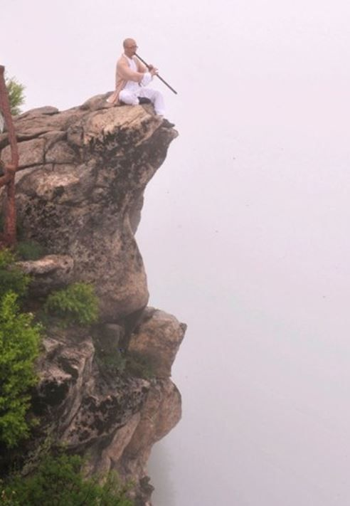 A hermit playing vertical flute on a cliff in Mt Zhongnan, Shaanxi province