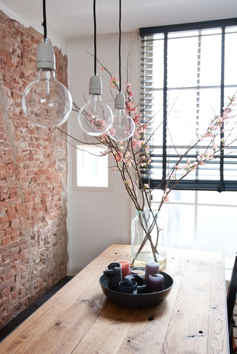 Vintage Backsteinwand im Loft Stil h ngende Gl hbirnen Lampen und blumige Tischdeko