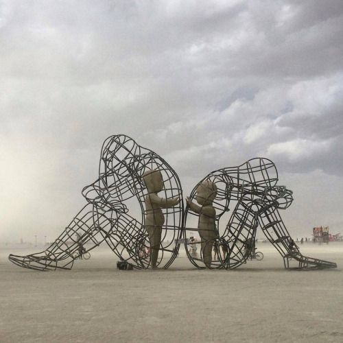 This sculpture by Ukranian artist Alexandr Milov highlighted during the Burning Man festival, 2015 | A structure 59 feet long,18 feet wide and 24 feet high, featuring two wire-frame adult figures in opposite direction,representing confilct,and inside of them two smaller,children-like figures,representing the adults inner self reaching for eachother.