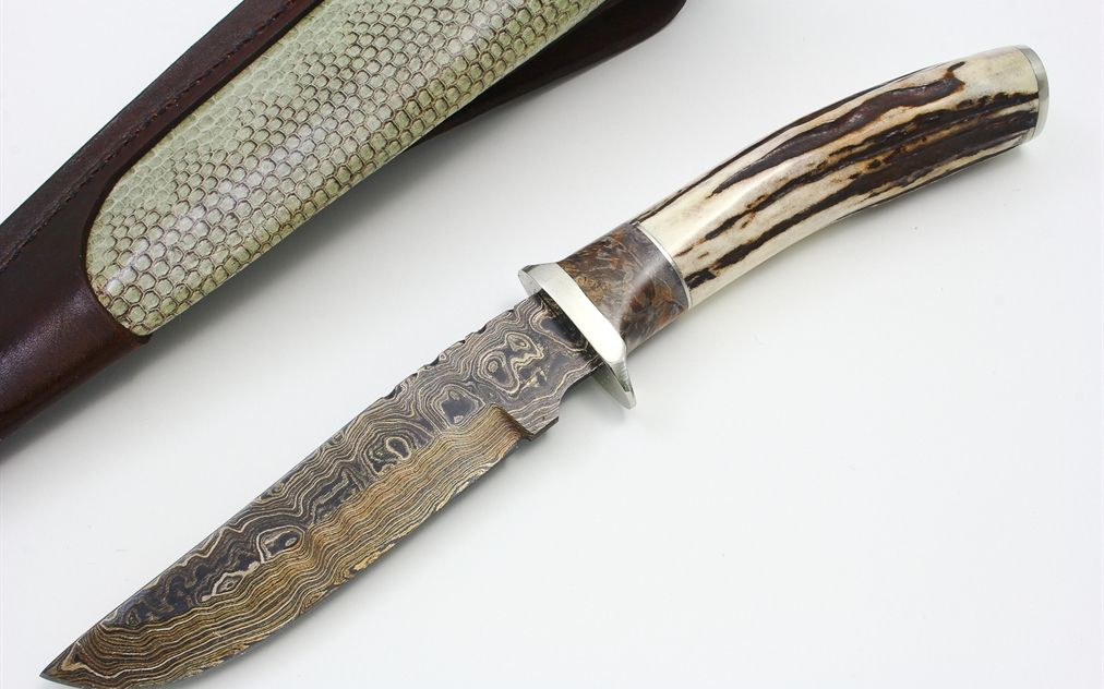 """By Herb Derr, this sole-authorship hunter features a random pattern Derr Damascus blade, mirror polished nickel silver guard and butt cap, a box elder burl spacer, and a Sambar stag handle. 3/16"""" blade thickness and 1 1/4"""" blade depth. File work on blade spine. Hidden tang construction. Outstanding look and feel. Superior craftsmanship throughout. Comes with hand tooled leather sheath with sea snake inlay. Brand new from maker from the 2012 New York Custom Knife Show. Overall Length 10.75"""""""