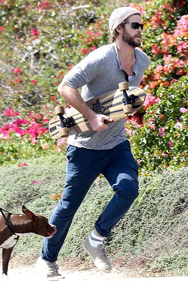 A beanie-clad Liam Hemsworth clutched his skateboard running up a hill in Malibu March 10.