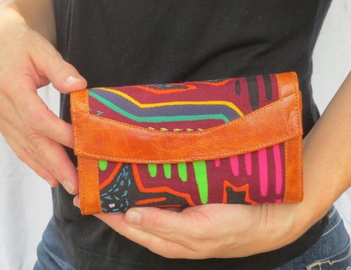 This is a stunning leather and mola wallet that is one of a kind! All of our products are fair trade and hand made from a family owned business in Colombia! These wallets use the finest grade leather and the craftsmanship is second to none! We guarantee you will love your purchase!