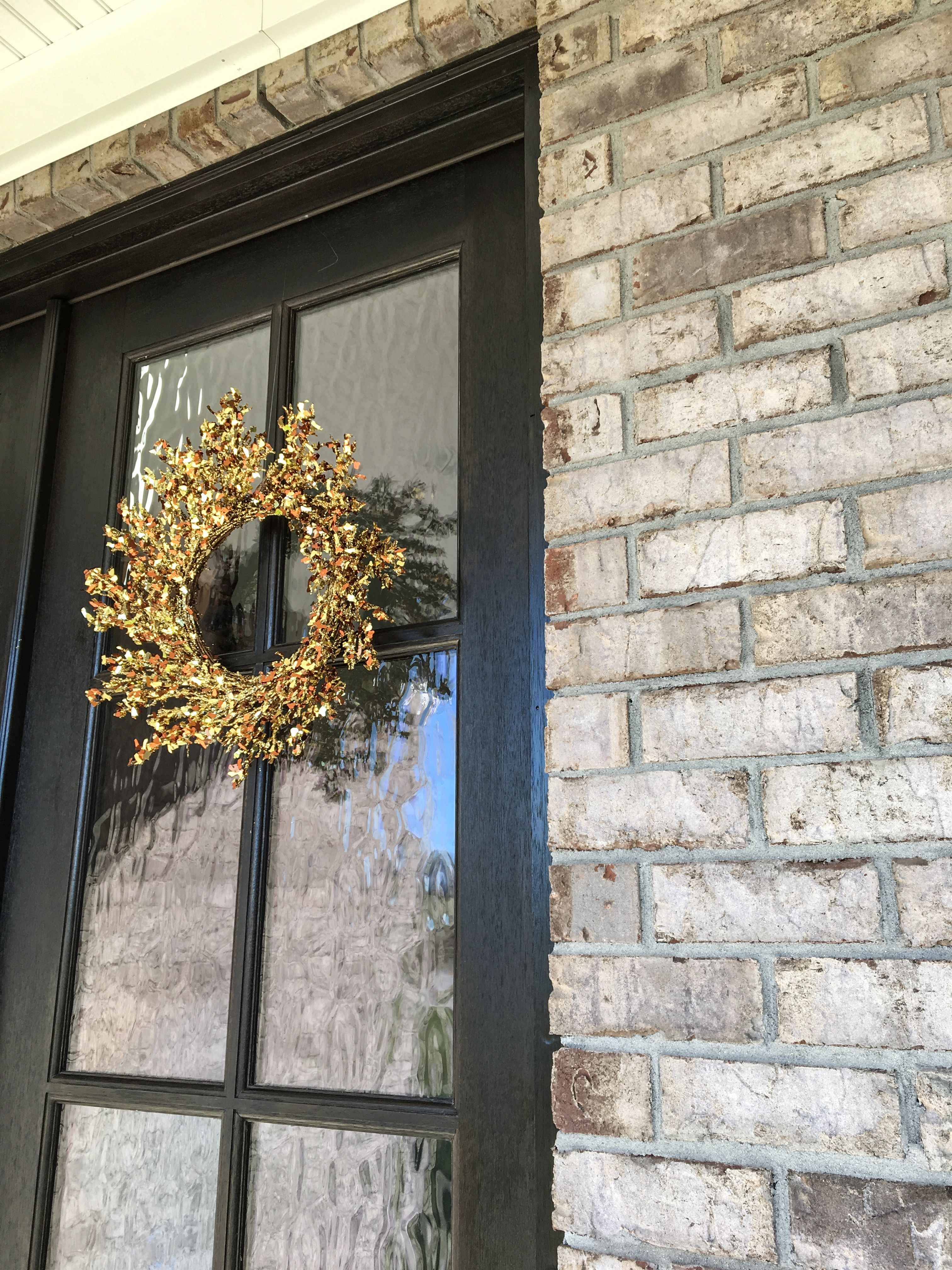 Style your home with grey castle brick and brown trim, topped with a gold metallic wreath for the holidays!