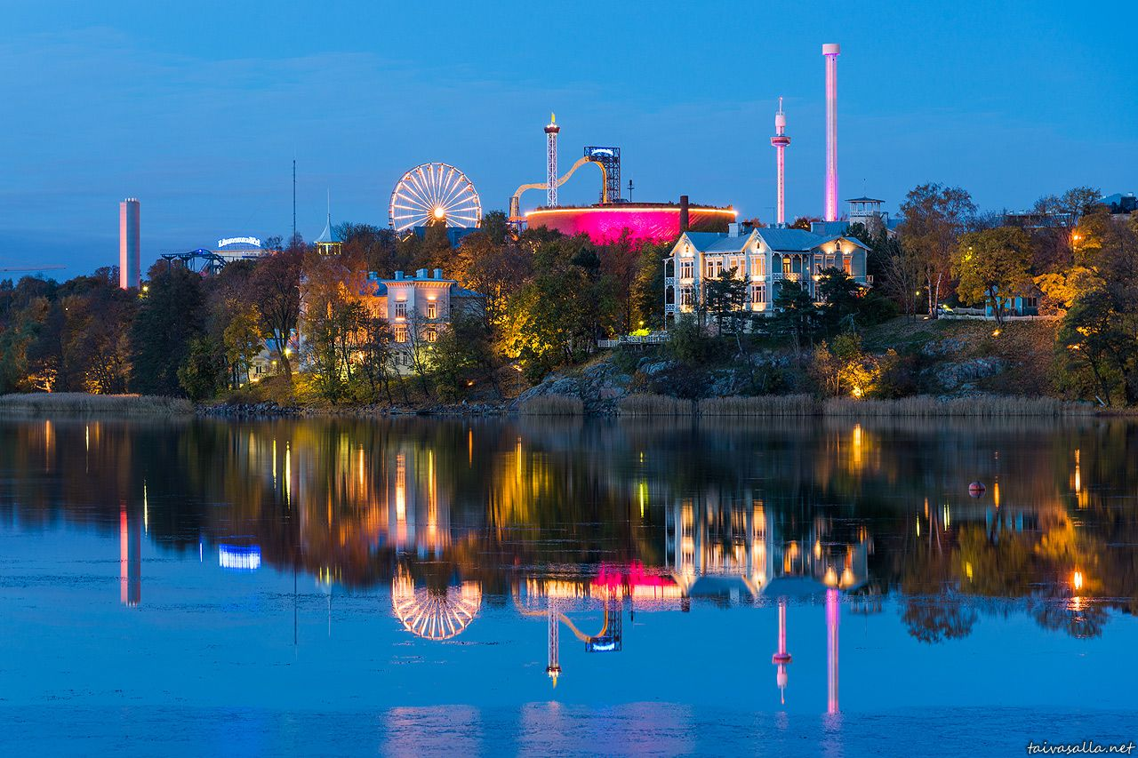 Helsinki, Finland: Linnanmäki amusement park and the Eläintarha villas seen across Töölönlahti inlet in the darkening autumn evening.