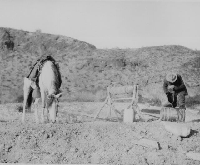A rider fills his keg from a desert well 30 miles north of Palomas, Arizona Territory. His horse refreshes himself nearby. By Stanton G. Smith, April 5, 1907. 95-FP-3-11.