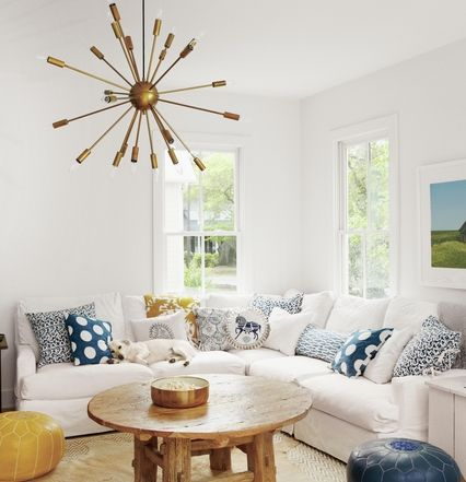 Family Room With White Sectional Blue And Throw Pillows Cowhide Rug Bold Light Fixture